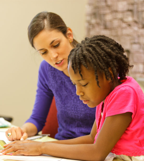 A speech-language pathology student works with a young client.