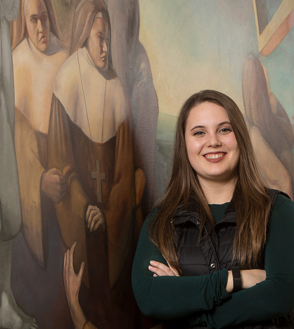 Kaylee Cunningham next to a campus mural