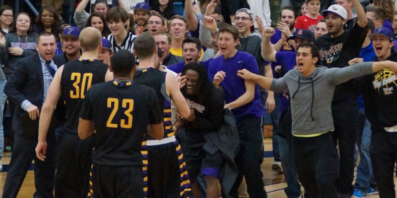 Basketball team celebrating with fans.