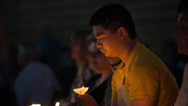 Male student holding candle during vigil.