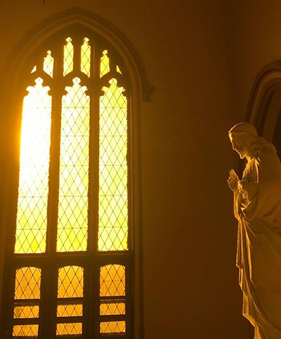 Jesus statue next to a window at Doerr Chapel.