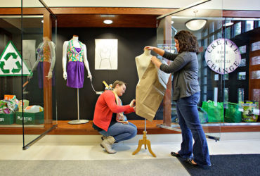 Fashion merchandising students working on display.