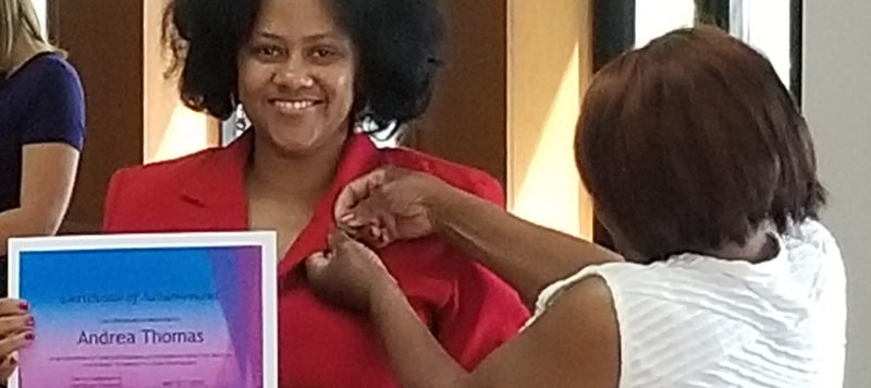 Student Andrea Thomas receives a pin from her family member in recognition of her success as a first-generation student.