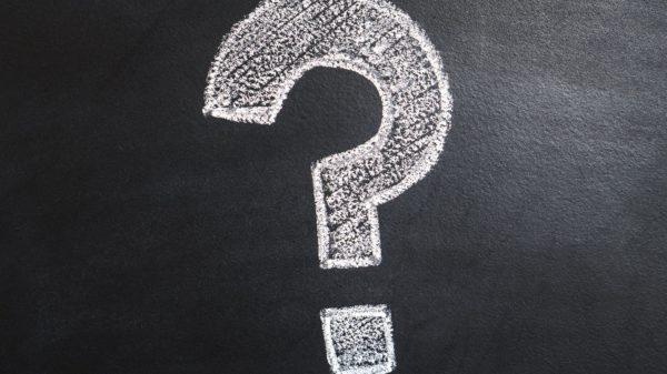 Question mark drawn in white chalk on blackboard